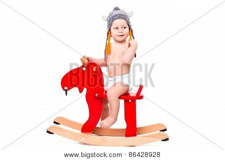 Baby in  hat on the toy elk