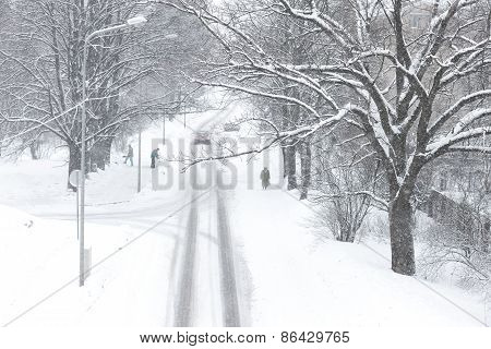 People Clean The Snow During A Snowfall In The Street