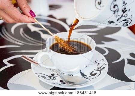 Coffee from a beautiful black and white teapot, pour into a cup on the table designer