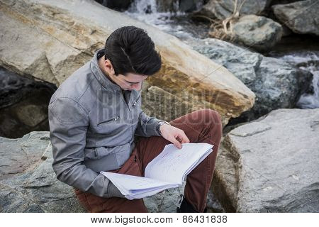 Young Male Student Studying Outdoors Sitting On Rocks