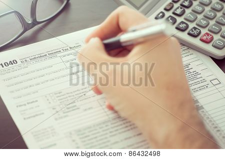 Man Filling Individual Income Tax Return Form