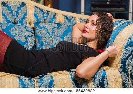 Portrait of beautiful romantic brunette on blue sofa.