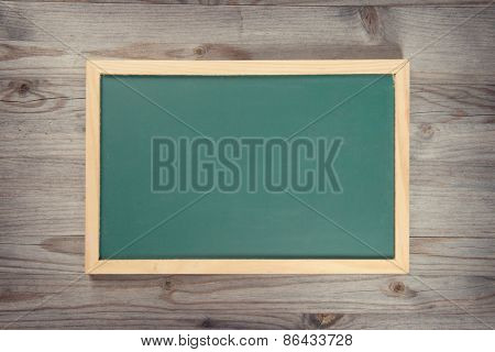 Empty blank green chalkboard with wooden frame on old wood background
