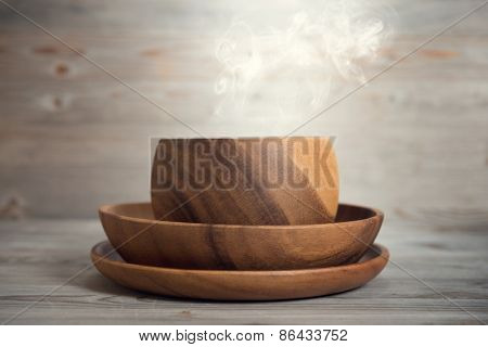 Empty bowl with hot smoke on old wooden table. Dramatic light.
