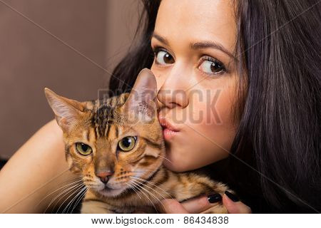 Brunette with bengal cat close-up.