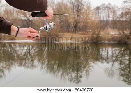 Fisherman with a fishing rod on the river bank