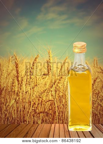 Vegetable Oil On Wooden Surface Against Of Wheat Ears.