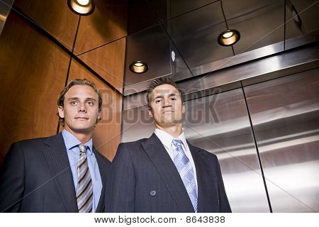 Businessmen Riding In Elevator
