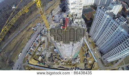 MOSCOW, RUSSIA - MAR 25, 2014: Tall crane works on construction site of dwelling complex near street with traffic at sunny spring day. Aerial view.