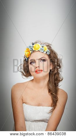 Portrait of beautiful girl in studio with yellow roses in her hair and naked shoulders