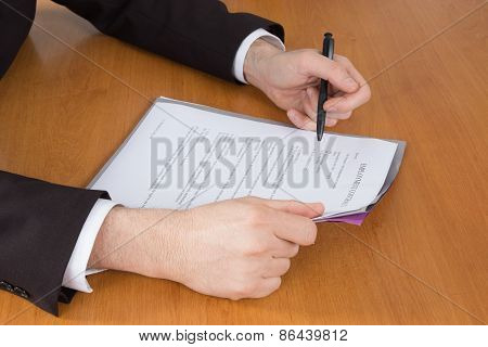 Businessman In Dark Suit And Blue Shirt Sitting At Office Desk Signing A Contract With Shallow Focus