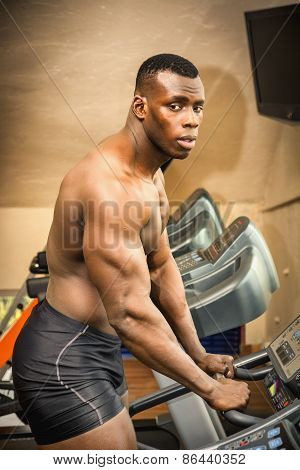 Muscular Black Male Bodybuilder Exercising On Treadmill In Gym