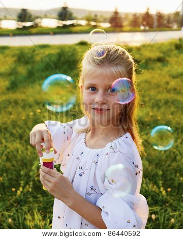 Happy Blonde Girl Blowing Soap Bubbles Outdoor At Sunset - Happy Carefree Childhood