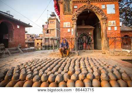 BHAKTAPUR, NEPAL - CIRCA DEC, 2013: Unidentified Nepalese man working in his pottery workshop. More 100 cultural groups have created an image of Bhaktapur as Capital of Nepal Arts.