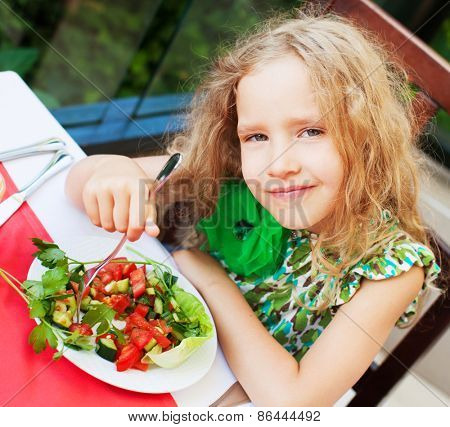 Child eating salad at a cafe. Girl eating outdoors