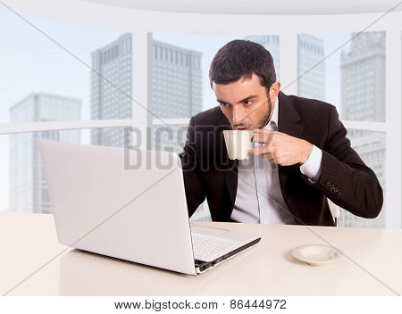Young Attractive Businessman Working At Business District Office Sitting At Computer Desk Drinking C