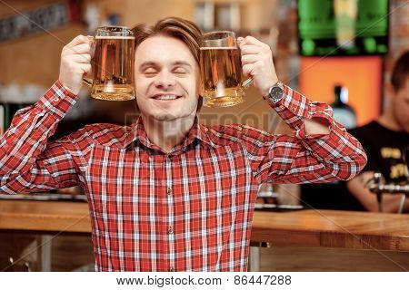 Young man with beer mugs