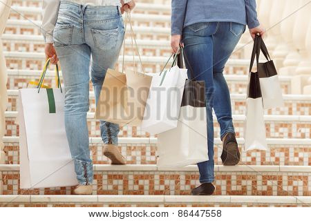 Girls going upstairs with shopping bags in hands
