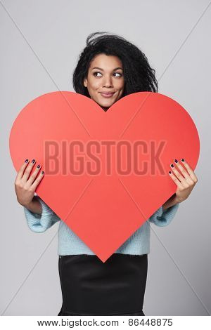 Girl holding big red heart shape