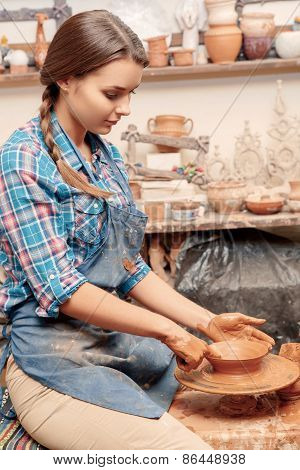 Woman works on pottery wheel
