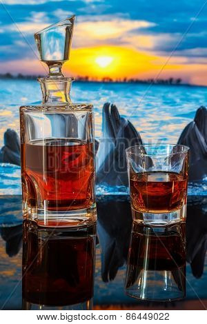 bottle of whiskey on a background of dolphins swim at sunset