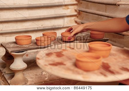Woman puts clay pots on the shelf