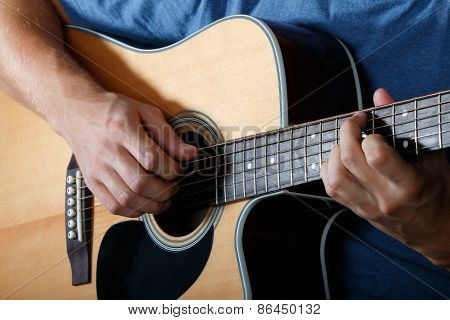 Man Performing Song On Acoustic Guitar