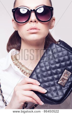 Closeup Of Fashionable Model In Sunglasses And Little Black Handbag