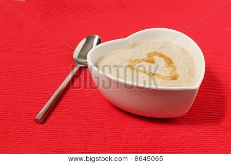 Porridge In A Heart Shape Bowl On Red Background