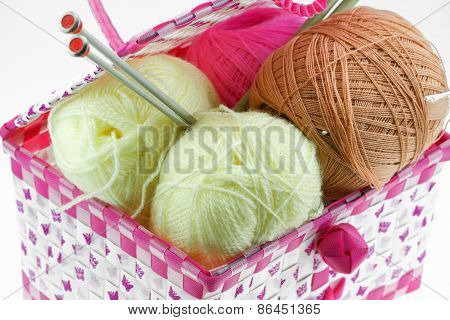 Colorful yarn balls in the basket isolated on white background