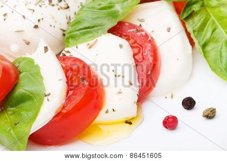 Caprese Salad. Mozzarella, Tomatoes And Basil Leaves