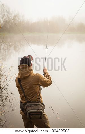 Fisherman on the river bank. Autumn fishing