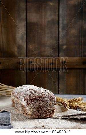 Loaf Of Bread With Wheat Spikelets On A Wooden Background