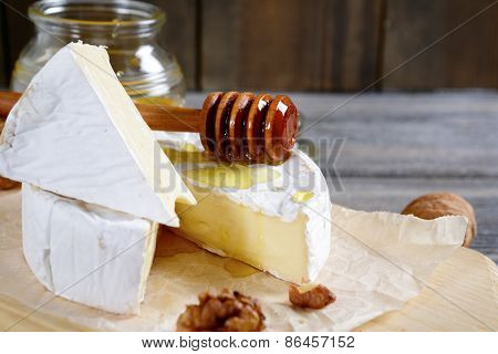 Cheese Camembert With Sweet Honey On A Wooden Board