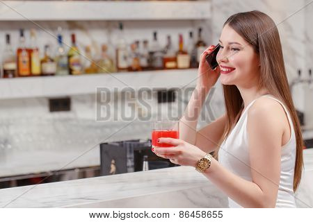 Woman speaks over the phone in bar