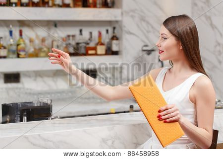 Woman holds a menu at the bar
