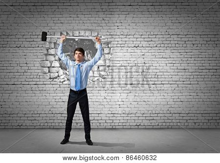 Young determined businessman with hammer in hands