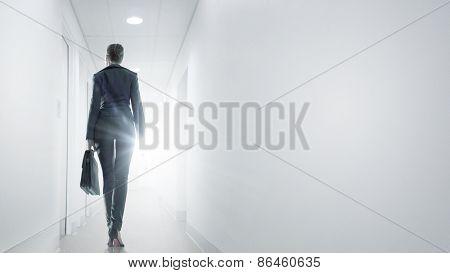 Rear view of businesswoman walking in office corridor