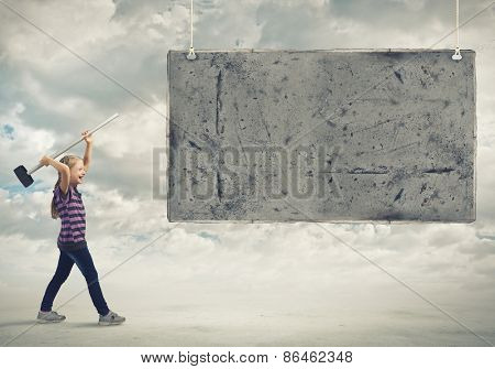 Cute little girl crushing cement banner with hammer