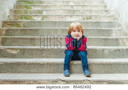 Adorable little boy with blond hair sitting on steps in a city