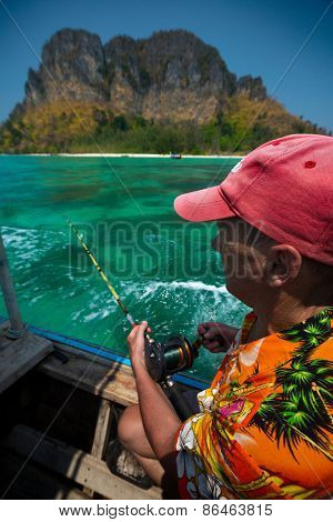 Mature man fishing in tropical sea from the boat at sunny day