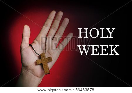 closeup of a wooden cross in the hand of a young caucasian man and the text holy week written in white on a red and black background