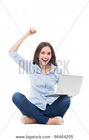 Woman raising arms in front of her laptop