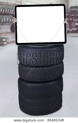 Man Holds Empty Board Above Tires