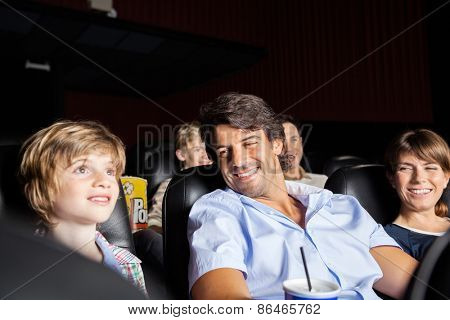 Happy parents looking at son watching movie in cinema theater
