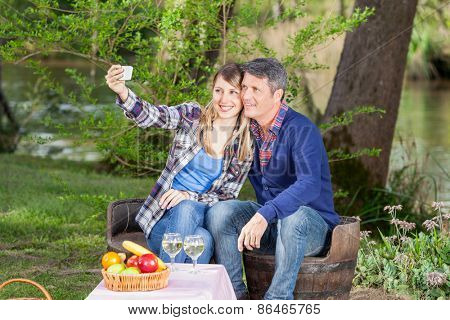 Smiling couple taking selfie with smartphone at campsite