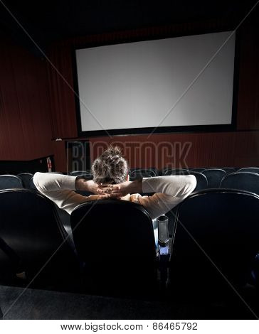 Rear view of relaxed man watching movie in cinema theater