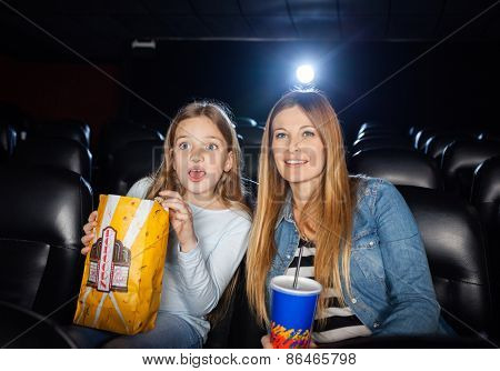 Surprised mother and daughter watching movie in cinema theater