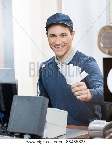 Portrait of happy male worker holding tickets at box office counter