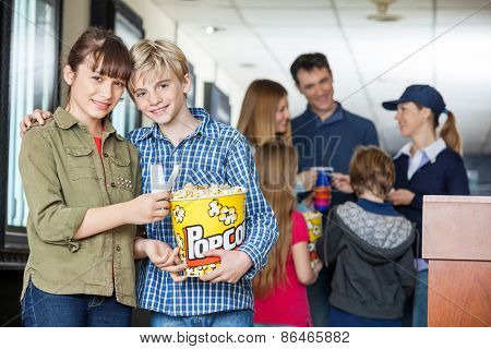 Portrait of affectionate brother and sister holding popcorn at cinema with family and worker in background